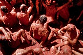 People sit in tomato pulp during La Tomatina festival in Bunol, Spain, 31 August 2006  La Tomatina is a tomato fight held annually in the town of Bunol, close to Valencia  Approximately 40,000 people from all over the world arrive to fight in the battle i