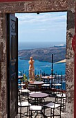 Looking down through doorway at romantic restaurant and the sea with statue in Santorini Greece in Greek Islands