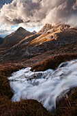 Dramatic play of light over a mountain torrent above the Bernina valley with the summits of Piz Albris (3137 m) and Piz Alo (2975 m) in the background, Engadin, Switzerland