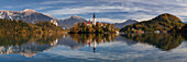 Picturesque view of St. Mary's Church and its reflection in the Lake Bled in autumn, in the background the castle of Bled soars in front of the Julian Alps, Gorenjska, Slovenia