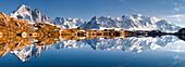 Panorama einer perfekten Spiegelung des Mont Blanc Massivs im Bergsee Lac de Chésery mit Auigelle Verte und Grande Jurasse im Herbst, Chamonix Tal, Haute-Savoie, Frankreich