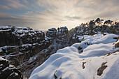 Fahles Licht über dem Nationalpark Sächsische Schweiz mit Blick auf die Wenzelwand und die Gerbingspitze im Winter, Sachsen, Deutschland