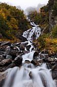 Impressive Waterfall in Val Bondasca on a foggy autumn day, Bergell, Switzerland