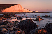 Photo of the impressive chalk cliffs of the Seven Sisters in the last light of the day above the bay of Cuckmere in the southern English county Sussex, England, Great Britain