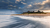 Incoming surf with the view to the impressive Bamburgh Castle in Northumberland, England, United Kingdom