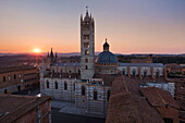 Sunset over the Cathedral of Siena Cattedrale di Santa Maria Assunta with its white and greenish-black marble, Siena, Tuscany, Italy