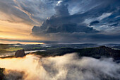Impressive thunderstorm above the Saxon Switzerland national park with the Falkenstein in the evening sun and fog in the valleys, Saxony, Germany