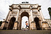 Female jogger passing Siegestor (vitory gate), Munich, Bavaria, Germany