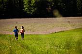 Zwei Jogger laufen über eine Wiese, Oberbayern, Deutschland