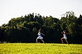 Zwei junge Frauen laufen über eine Wiese, Oberbayern, Deutschland