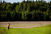 Young woman jogging over a meadow, Upper Bavaria, Germany