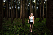 Young woman wearing business suit in a forest, Bavaria, Germany