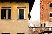 Senior man looking out of a window, Piazza Erbe, Verona, Veneto, Italy