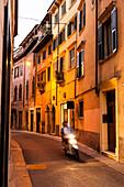 Motor scooter passing a lane in the historic center, Verona, Veneto, Italy
