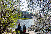 Two young woman sitting on a wall, Binnenalster of Hamburg in springtime, Hamburg, Northern Germany, Germany