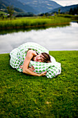 Woman lying with bedding on a golf course, Styria, Austria
