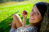 Young woman holding an apple leaning against a tree, Styria, Austria