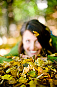 Young woman lying in autumn leaves, Styria, Austria