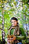 Young woman holding autumn leaves in hands, Styria, Austria