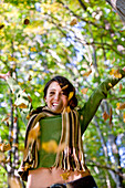Young woman throwing autumn leaves in the air, Styria, Austria