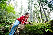Mädchen betrachtet Pflanzen durch einen Lupe, Steiermark, Österreich