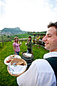 Two young woman enjoying local specialties in a vineyard, Riegersburg, Styria, Austria