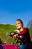 Young woman with a glass of white wine sitting on a tractor, Styria, Austria