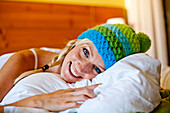 Young woman wearing a wolly hat lying in a bed, Fladnitz an der Teichalm, Styria, Austria