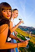 Two young women drinking white wine, Gamlitz, Styria, Austria