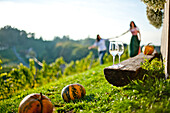Two wine glasses on a bench, two young women in background, Styria, Austria