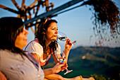 Two young women drinking white wine, Styria, Austria