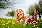 Young woman lying at a dandelion meadow, Stubenberg, Styria, Austria