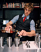 USA, California, Los Angeles, bartender making drink at Comme Ca Restaurant.
