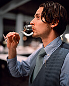 USA, California, Los Angeles, sommelier trying wine at Osteria Mozza.