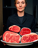 USA, California, Los Angeles, young waitress standing holding the meat tray at CUT Restaurant.