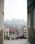 CHINA, Macau, Cityscape and crowd through ruins of St. Paul, 17th century, Cathedral, UNESCO world heritage site, catholic