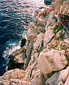 CROATIA, Dubrovnik, Dalmatian coast, the Buza Bar at the edge of the cliff with guests sitting to watch the sunset.
