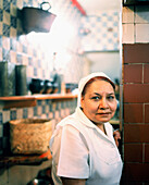 MEXICO, Mexico City, female chef standing in kitchen of Fonda El Refugio.