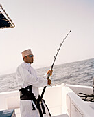 OMAN, Muscat, young man in traditional clothing fishing on boat