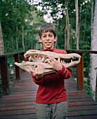 PERU, Amazon Rainforest, South America, Latin America, portrait of Asa Conover carrying a Cayman skull at the Posada Amazonas Lodge.