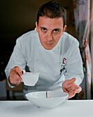 SPAIN, Ezcaray, chef Francis Paniego plating a dish at his restaurant, El Portal De Echaurren.