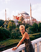 TURKEY, Istanbul, smiling lady looking away with the Aya Sofya mosque in the background. She is standing on the roof balcony of the Four Seasons Hotel.