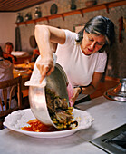 TURKEY, chef, writer, Engis Akin pouring a Turkish cuisine in a large plate in her kitchen.