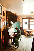ALASKA, Talkeetna, Jared Wayne Kesler a piano player and employee at the Historic Fairview Inn (1923), playing his song Animal Grave
