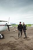 ALASKA, Homer, a couple stand in front of a small plane on the beach at Hallow Bay, Katmai National Park, Katmai Peninsula, Gulf of Alaska