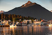 ALASKA, Sitka, a peaceful view of homes and fishing boats along the shore in Sitka Harbor at sunset, Mount Verstovia peak in in the distance