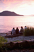 ALASKA, Sitka, people enjoy the sunset and sit on a log at Halibut Cove, Sitka Sound