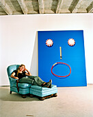 USA, Arizona, female artist relaxes in armchair next to her painting starry eyes, Winslow