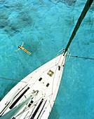 ARUBA, woman swimming in Caribbean Sea by a sailboat, Palm Island