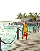 ARUBA, portrait of young woman standing on a dock with her snorkel gear, Renaissance Island